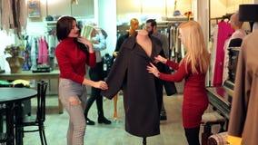 Un groupe d'amis choisissent des vêtements à un grand centre commercial banque de vidéos