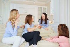 Un groupe d'amis de jeunes filles parlent lors d'une réunion dans une chambre Photographie stock