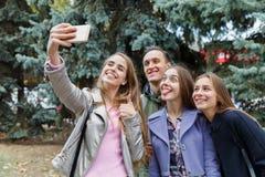 Un groupe d'amis de sourire prenant un téléphone portable sont photographiés dehors Photographie stock libre de droits