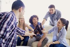 Un groupe d'amis font tinter des bouteilles lors d'une réunion dans la chambre Photo stock