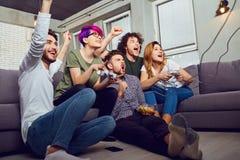 Un groupe d'amis jouant des jeux vidéo se reposant sur le divan, dedans Photo libre de droits