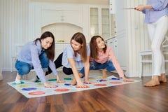 Un groupe d'amis jouent dans les jeux sur le plancher à l'intérieur Photos stock