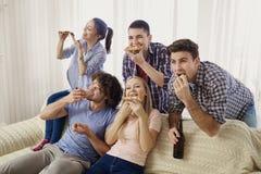 Un groupe d'amis mangeant de la pizza tout en se reposant sur le divan Photo stock