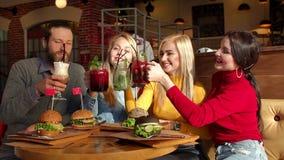 Un groupe d'amis mangent des hamburgers en restaurant et cocktails de baie de boissons banque de vidéos