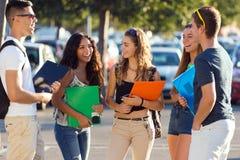 Un groupe d'amis parlant dans la rue après classe Image libre de droits