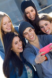 Un groupe d'amis prenant des photos avec un smartphone Photos stock
