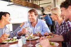 Un groupe d'amis prenant le déjeuner dans un restaurant Images libres de droits