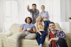 Un groupe d'amis regardant la TV dans la chambre Images libres de droits