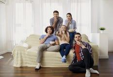 Un groupe d'amis regardant la TV dans la chambre Photos stock