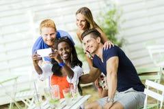 Un groupe d'amis reposant une table et parlant le sourire tandis que merci Photographie stock