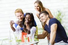 Un groupe d'amis reposant une table et parlant le sourire tandis que merci Photo stock