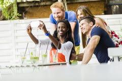 Un groupe d'amis reposant une table et parlant le sourire tandis que merci Photo libre de droits