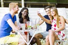 Un groupe d'amis reposant une table et parlant le sourire tandis que merci Images libres de droits