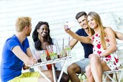 Un groupe d'amis reposant une table et parlant le sourire tandis que merci Image stock