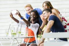 Un groupe d'amis reposant une table et parlant le sourire tandis que merci Image libre de droits