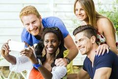 Un groupe d'amis reposant une table et parlant le sourire tandis que merci Images stock