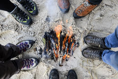 Un groupe d'amis se tenant autour d'un feu sur une plage Image libre de droits