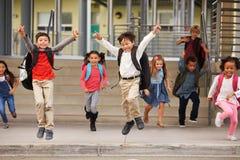 Un groupe d'école primaire énergique badine quitter l'école Photos libres de droits