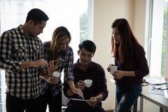 Un groupe d'hommes et de femmes d'affaires parlant entre eux Ayez a Photo libre de droits