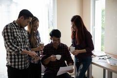 Un groupe d'hommes et de femmes d'affaires parlant entre eux Ayez a Photos stock