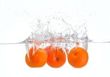 Oranges éclaboussant dans l'eau photographie stock