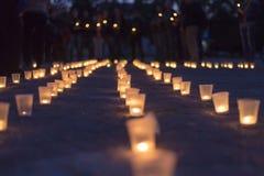 Un groupe de bougies brûlant dans la rue et les personnes tenant des bougies à l'arrière-plan Jour de la mémoire du privé image stock