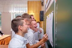 Un groupe de camarades de classe dessine sur un tableau noir photos stock