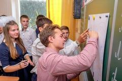 Un groupe de camarades de classe dessine sur un tableau noir avec un stylo feutre image libre de droits