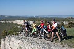 Un groupe de cinq adultes sur des bicyclettes. Image libre de droits