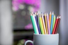 Un groupe de couleur crayonne dans une tasse blanche Photos libres de droits