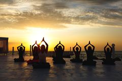 Un groupe de femmes faisant le yoga au lever de soleil près de la mer photos stock