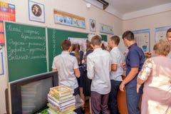 Un groupe de filles et de garçons de camarades de classe dessine sur un tableau noir photo libre de droits