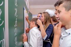 Un groupe de filles et de garçons de camarades de classe dessine sur un tableau noir vert images stock