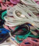 Un groupe de fils colorés pour différents téléphones images libres de droits