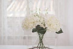 Un groupe de fleurs blanches dans un pot en verre Image stock