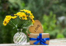 Un groupe de fleurs jaunes, d'un cadeau et d'un coeur en bois Concept romantique Photos libres de droits
