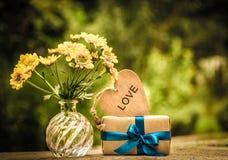 Un groupe de fleurs jaunes, d'un cadeau et d'un coeur en bois Concept romantique Teinture de vintage Images libres de droits