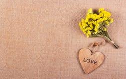 Un groupe de fleurs jaunes et un coeur en bois sur un fond de toile naturel Concept romantique Photos stock