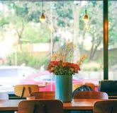 Un groupe de fleurs rouges décorées dans le vase en céramique bleu sur en bois images stock