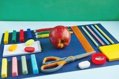 Un groupe de fournitures scolaires sur un fond bleu Photos stock