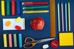 Un groupe de fournitures scolaires sur un fond bleu Image stock