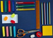Un groupe de fournitures scolaires sur un fond bleu Image libre de droits