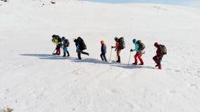 Un groupe de grimpeurs se composant de sept personnes avec toute la ténacité essayant de surmonter les congères et le temps banque de vidéos