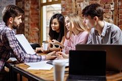Un groupe de jeunes créatifs discutant un nouveau projet Image libre de droits