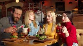 Un groupe de jeunes et gais amis mangent les hamburgers d?licieux dans un caf? ? la mode banque de vidéos