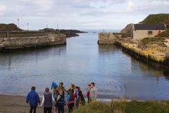 Un groupe de jeunes reçoit des instructions du chef de groupe avant la participation aux sports aquatiques au port dans Ballintoy Photographie stock libre de droits
