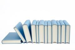 Un groupe de livres bleus dans une rangée sur un fond blanc Photos libres de droits