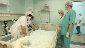 Un groupe de médecins relient le dispositif pour chauffer le patient après l'opération banque de vidéos
