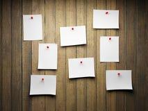 Un groupe de notes de rappel goupillées à un mur en bois Photos libres de droits