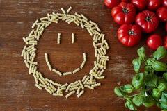 Un groupe de pâtes sous la forme d'un visage souriant Photos libres de droits